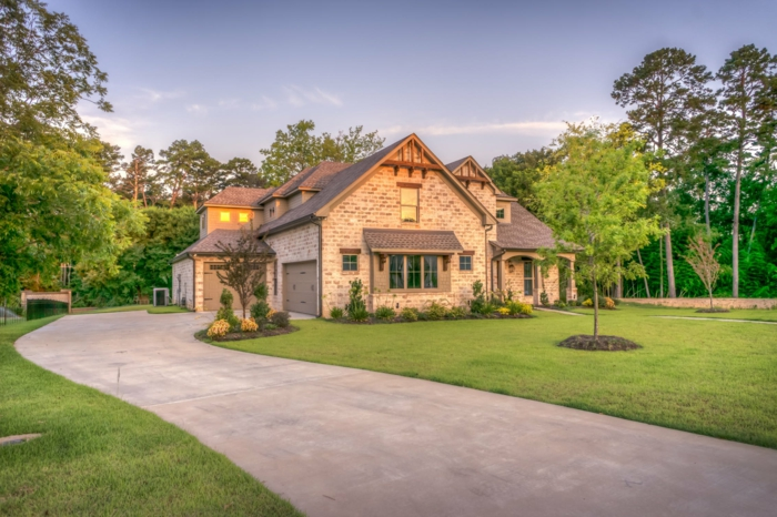 ein kleines Traumhaus mit Garten, ein grüner Rasen, leuchtende Fenster, Hausfinanzierung