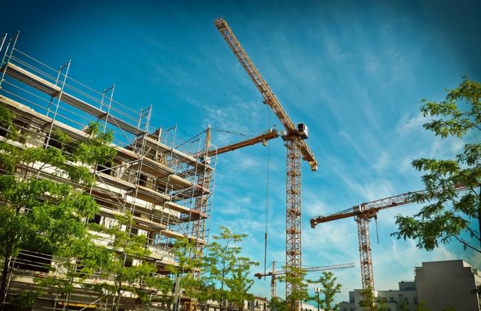 Hier sieht man, wie ein Haus gebaut wird, ein blauer Himmel, kleine Bäume, Hausfinanzierung