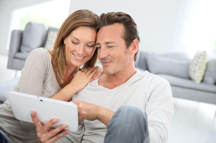 ein Mann und eine Frau sehen Tablet, suchen Sie nach der Traumwohnung, Hausfinanzierung
