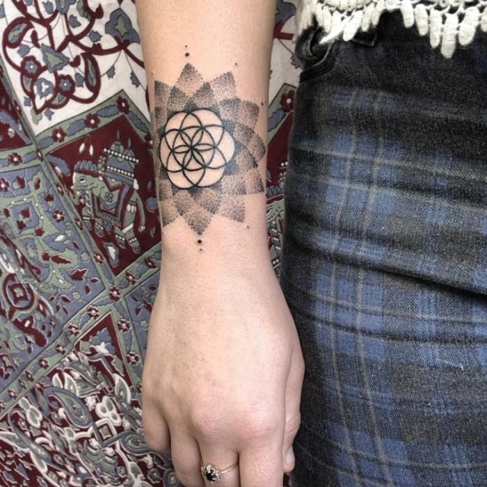 blume des lebens tattoo, eine schöne tattooidee auf dem unterarm, ring am mittelfinger