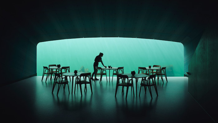 großes panoramafenster eines unterwasser-lokals mit vielen stühlen und tischen aus holz, eine junge frau