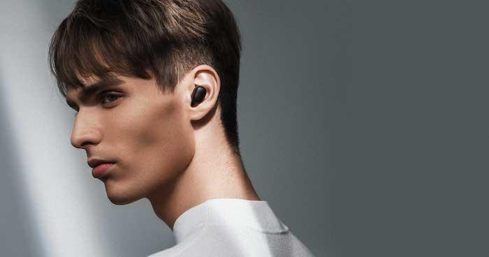 junger mann mit kleinen schwarzen kabellosen ohrhörern von xiaomi, redmi airdots bluetooth