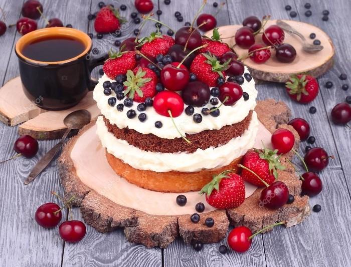 joghurt sahne torte, kaffee tasse, kleine löffel daneben, mehrschichtige torte mit sahne creme und frischen früchten, kirschen, erdbeeren, heidelbeeren