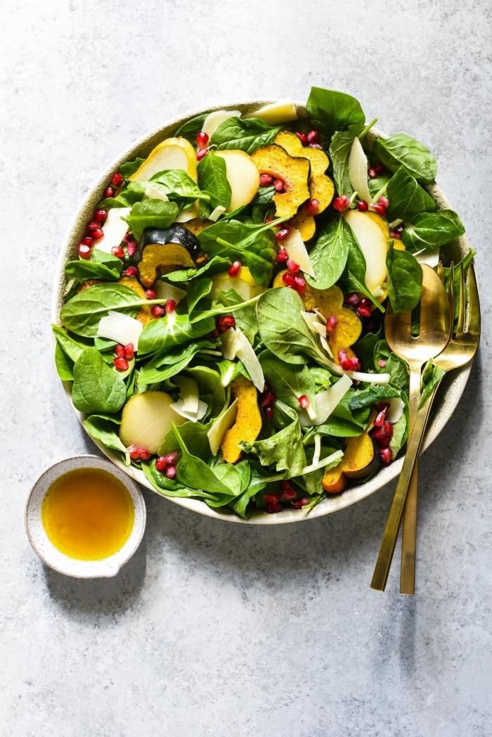 kohlenhydratfreis essen, gesunder salat mit spinat und granatapfelsamen, goldenes geschirr