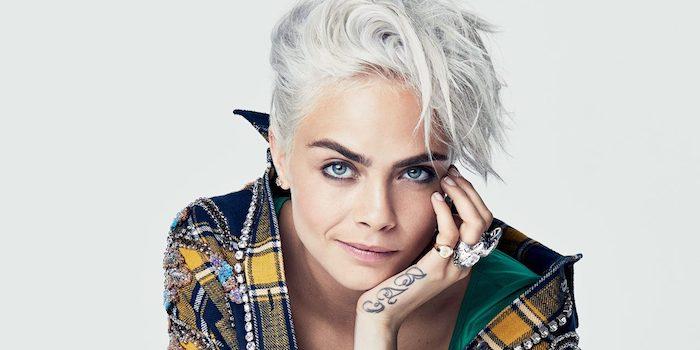 Cara Delevingne Kurzhaarfrisur, lässiger Hairstyle, Tattoo an der Hand, karierter Mantel mit Steinen