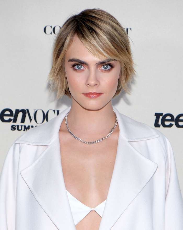 Cara Delevingne Haarschnitt, Stufenschnitt, oben länger, hinten kürzer, mit blonden Strähnchen, weißes Outfit