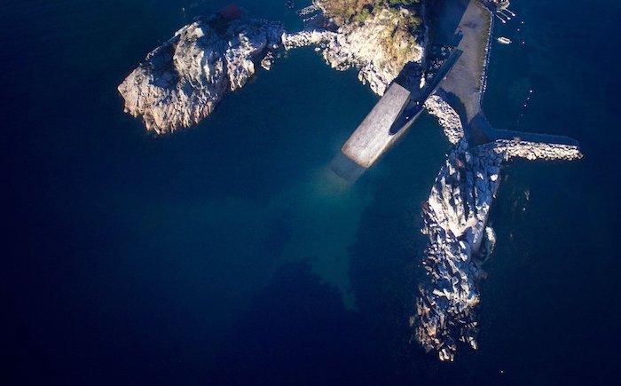 küste mit steinen, meeer mit blauem wasser, ein unterwasser-restaurant aus beton und holz, erstes unterwasser-restaurant in europa