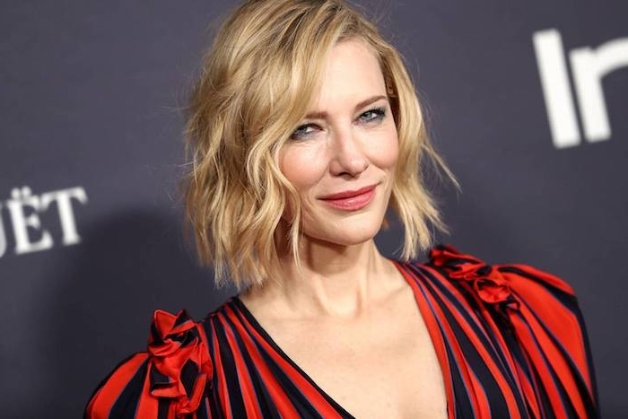 Cate Blanchett Haarschnitt, Bob Haarschnitt mit seitlichem Scheitel, blonde wellige Haare, gestreiftes Kleid in Rot und Schwarz