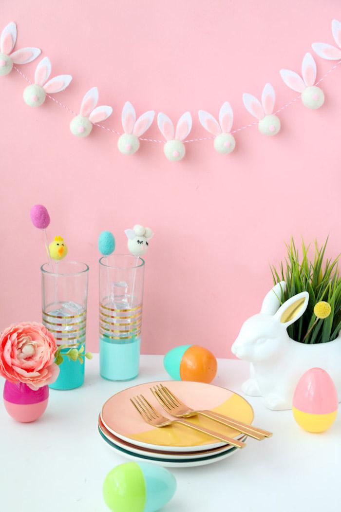 Osterdeko selber machen, Girlande mit kleinen Osterhasen, bunte Plastikeier und Blumentopf in der Form von Osterhase