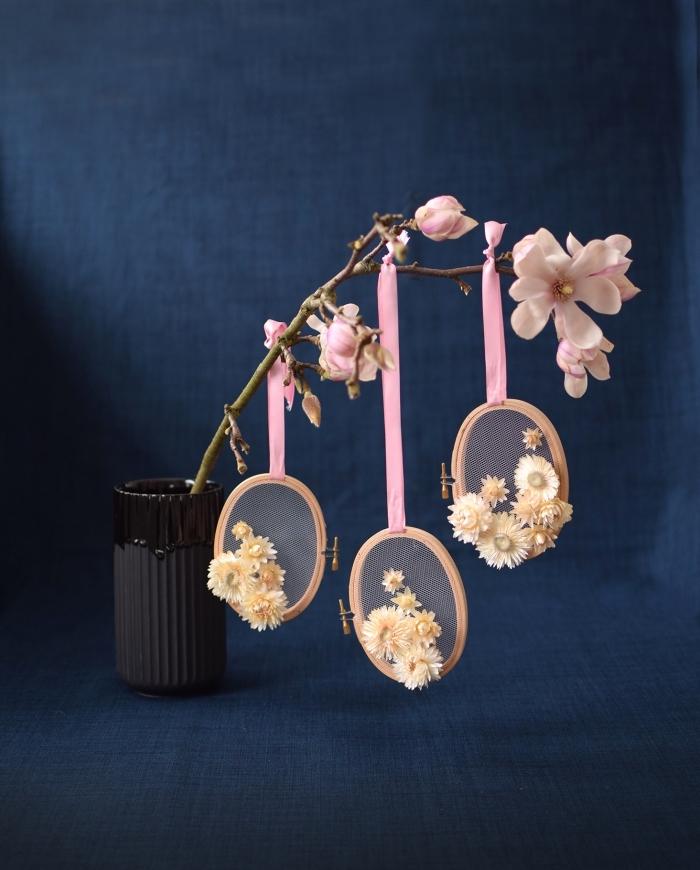 osterdeko selber basteln, selbstgemachte dekorationen aus stickrahmen, papierblumen und rosa schleife