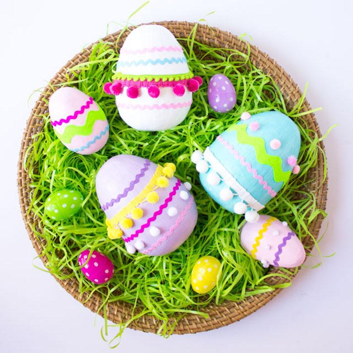 Osterbasteln mit Kleinkindern, Holzeier mit Acrylfarben bemalen, Dekoband und Bommeln kleben