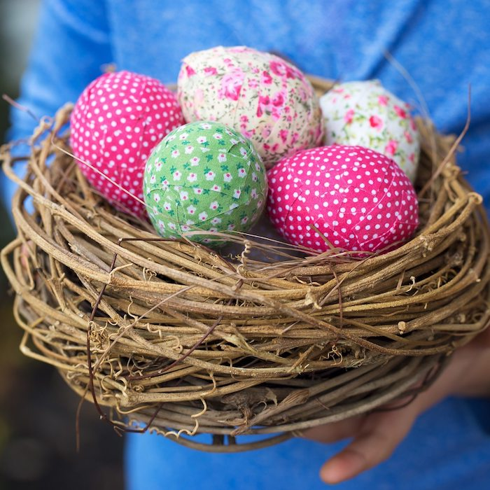 Osternest voll mit bunten Ostereiern, Osterdeko selber machen, Ostereier mit kleinen Stücken Papier bekleben