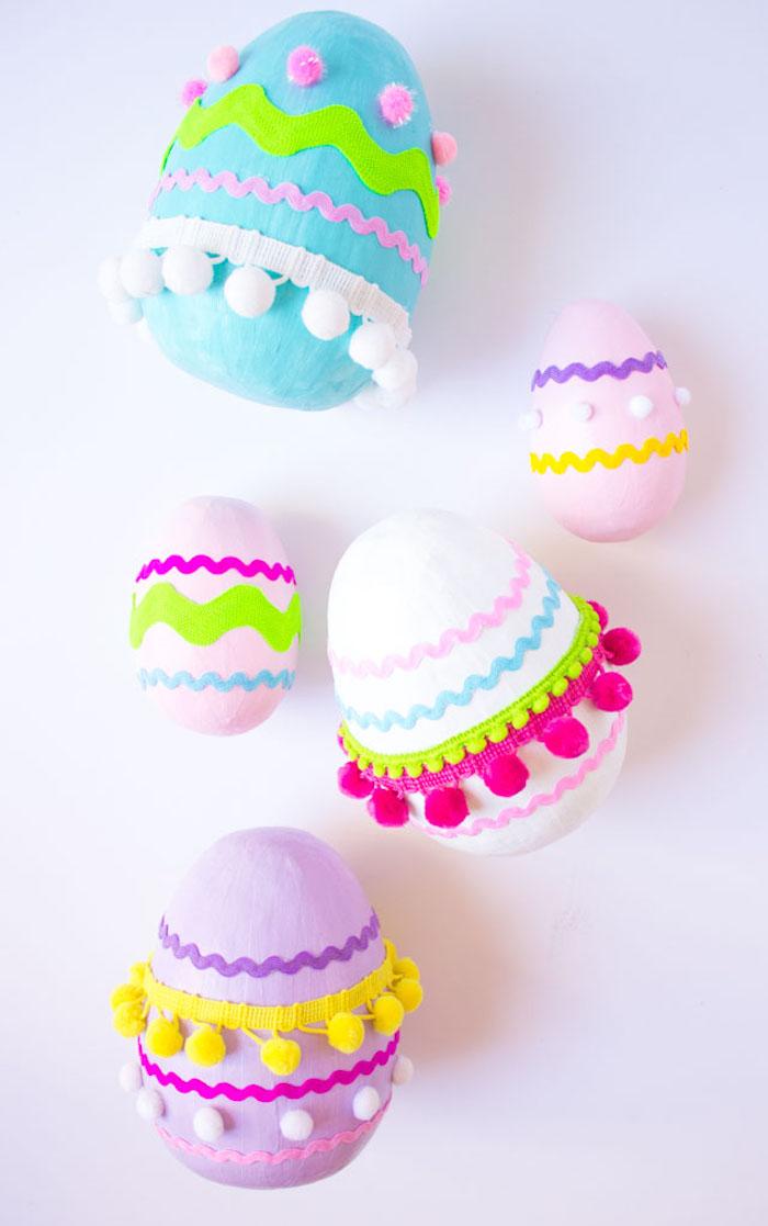 Holzeier zu Ostern bemalen, Stücke Dekoband und kleine Bommeln kleben, Bastelideen für Kleinkinder