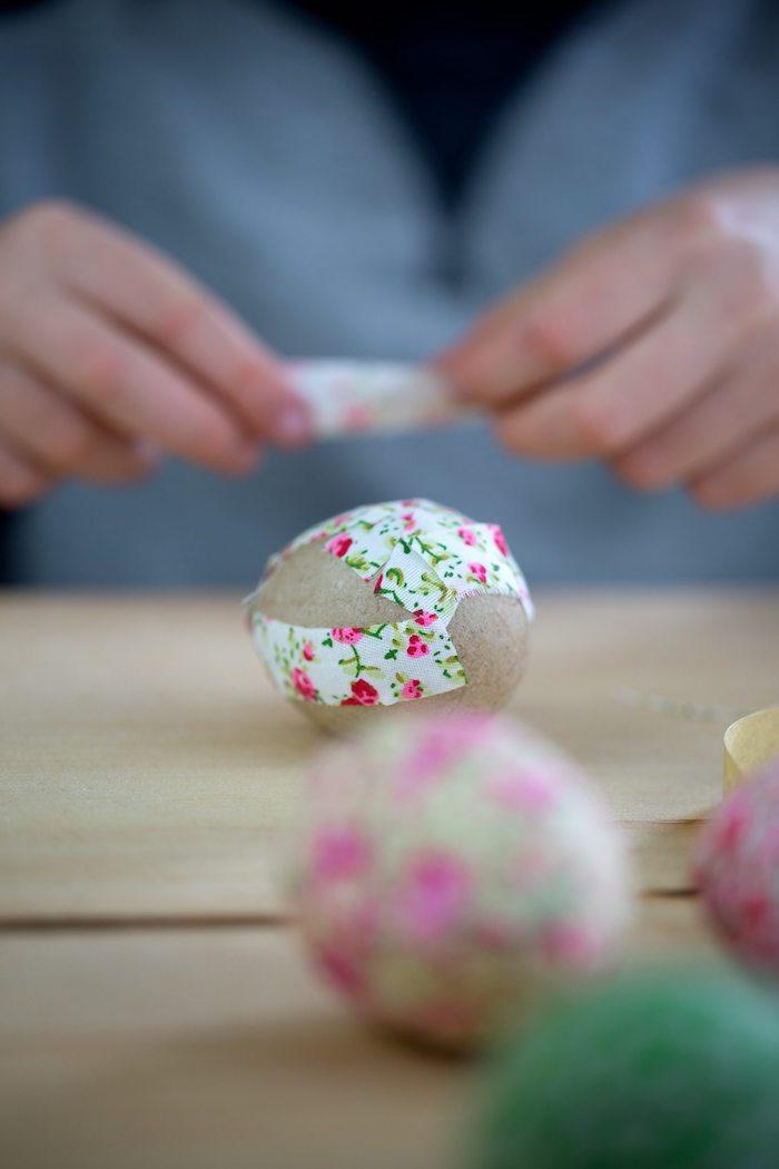 Kleine Stücke Papier ausschneiden, Ostereier aus Holz bekleben, mit Blumenmuster