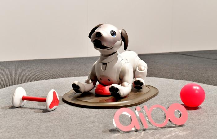Spielzeuge und Aibo Roboter Hund, der zum Aufladen steht, Aibo Spielzeuge