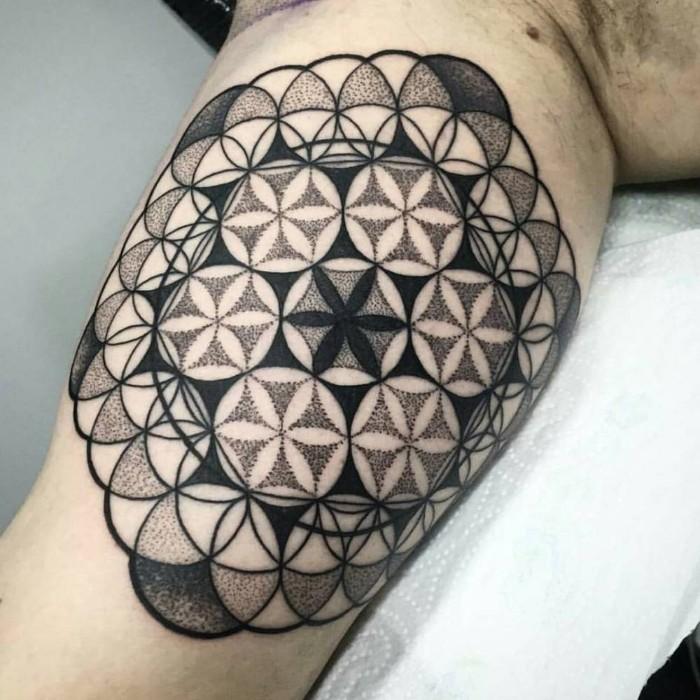 tribal tattoo auf dem oberarm, blumen und eine kette von designs, die alle zusammen gehören und ein ganzes bilden