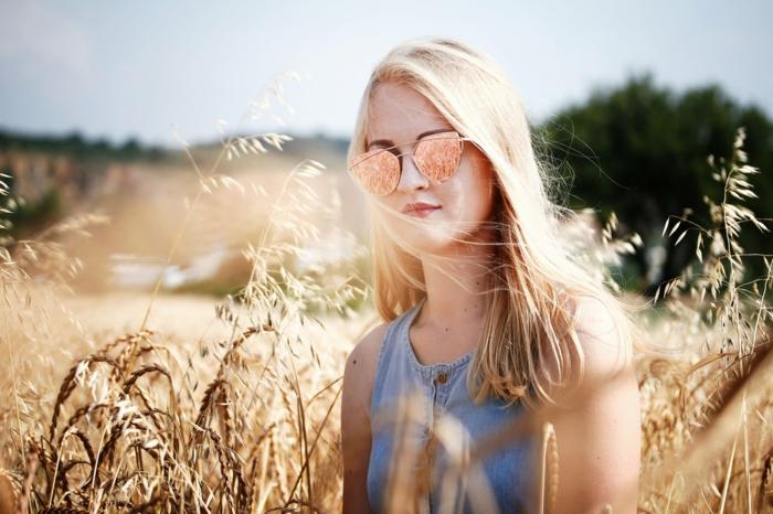 ein Mädchen mit langem, blondem Haar, verspiegelte Sonnenbrille in einem Feld
