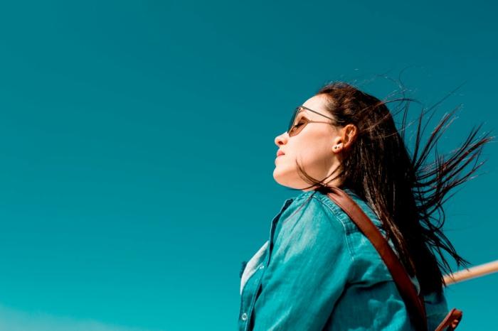 ein Mädchen mit langem, braunem Haar, das der Wind weht, Sonne und Sonnenbrillen