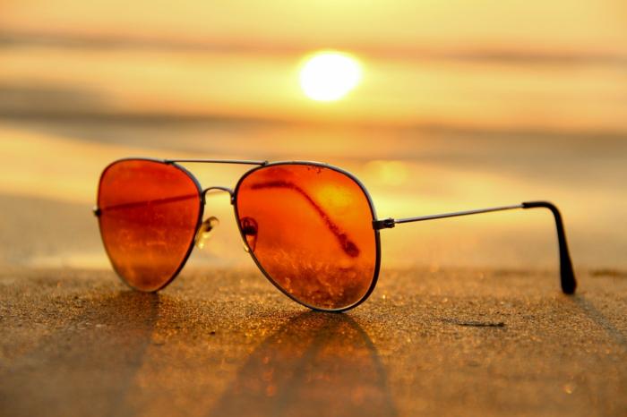 Ray Ban Sonnenbrille mit roten Gläsern, beim Sonnenuntergang auf einem Strand
