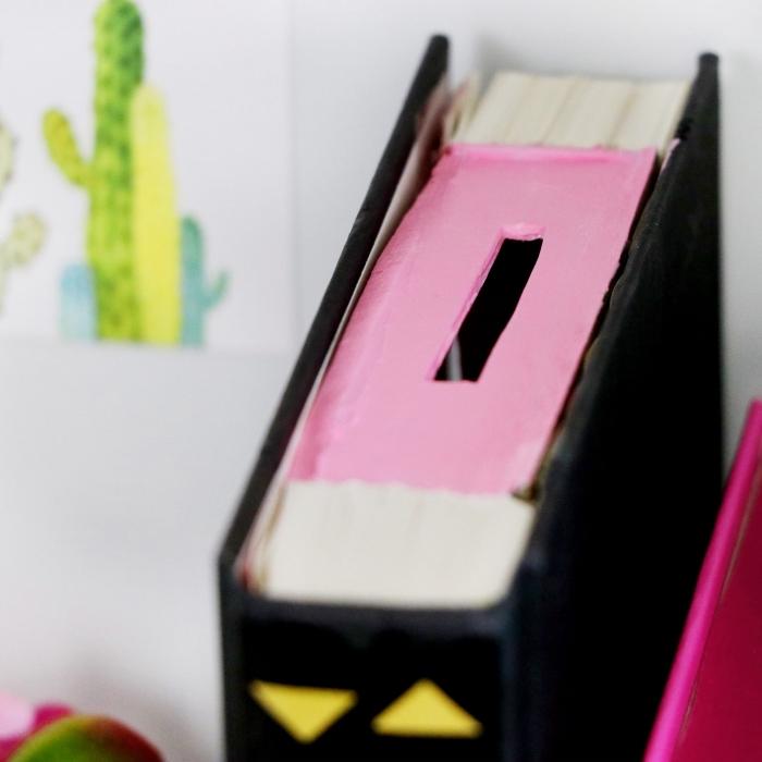 spardose selbst gestalten, buch mit schwarzem buchdeckel, rosa klebeband, bücher upcyceln