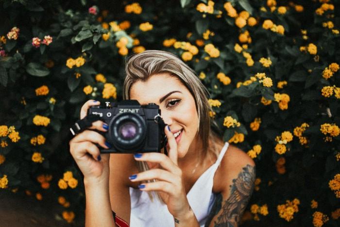 schöne tattoos auf dem oberarm von einer jungen frau, fotografin, kamera, fotos machen, weißes kleid