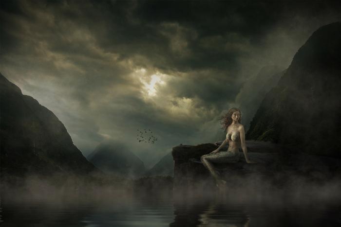 ein Himmel mit schwarzen Wolken bedeckt, ein Meeresjungfrau auf den Felsen, Sonne zeigt sich zwischen die Wolken, hübsche Bilder