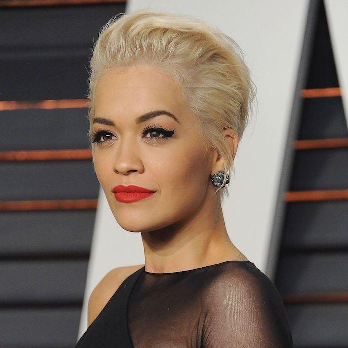 Rita Ora Kurzhaarfrisur, blonde Haare, roter Lippenstift und schwarzer Lidstrich, schwarzes Kleid