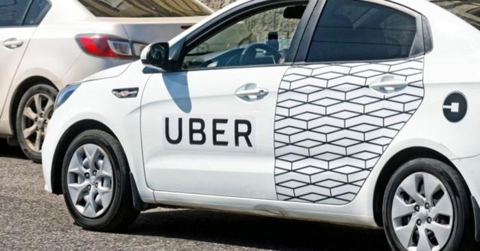 ein weißes Auto mit der Aufschrift Uber mit gemusterte Tür, ein Logo von Uber darauf