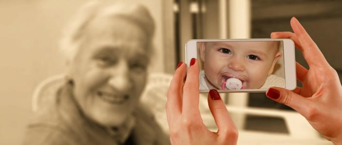 eine Frau nimmt Foto von Großmutter auf, auf dem Display ist ein Bild von Baby, hübsche Bilder