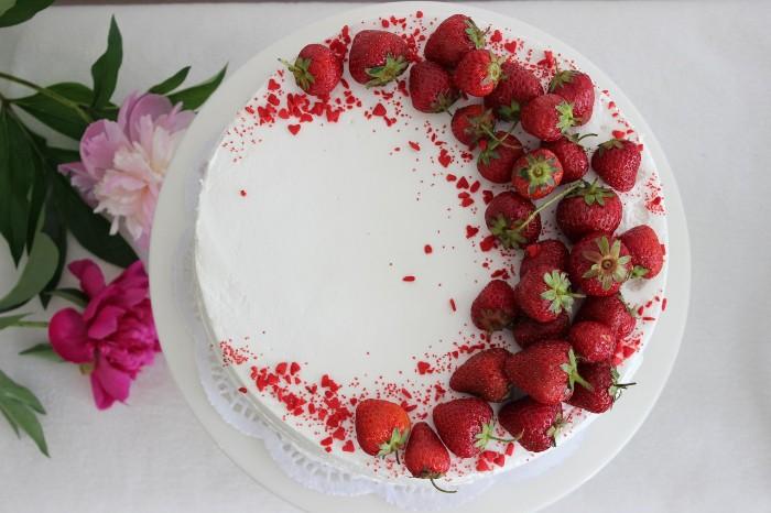 einfache erdbeertorte zum nachmachen, weiße creme dekoriert mit frischen erdbeeren, zwei rosaroten blumen daneben deko kreativ