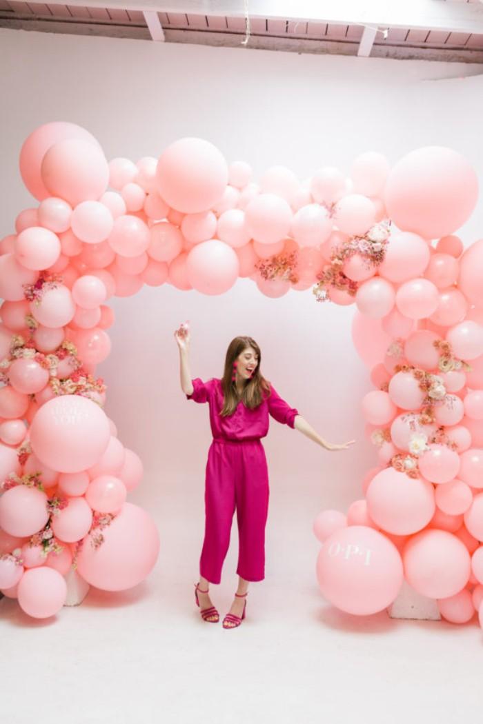 erdbeer joghurt torte, eine frau mit rosarotem jumpsuit, absatzschuhe, balloons, braune haare