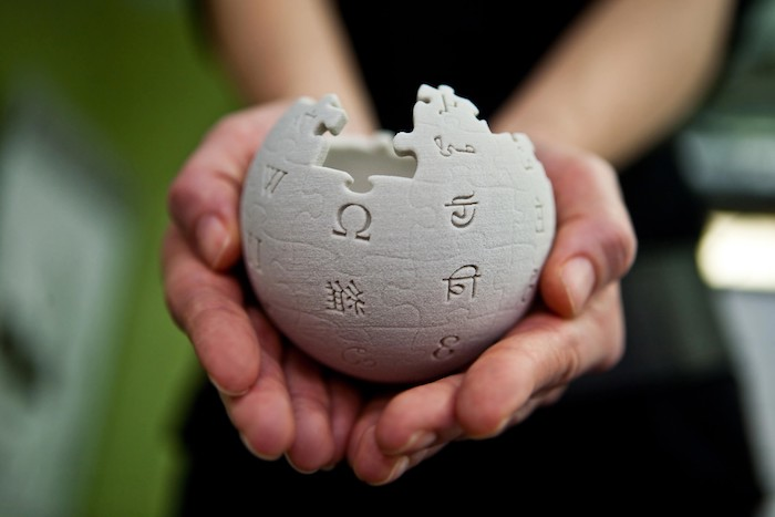 der weiße kleine modulare globus, der logo von wikipedia, zwei hände einer jungen frau