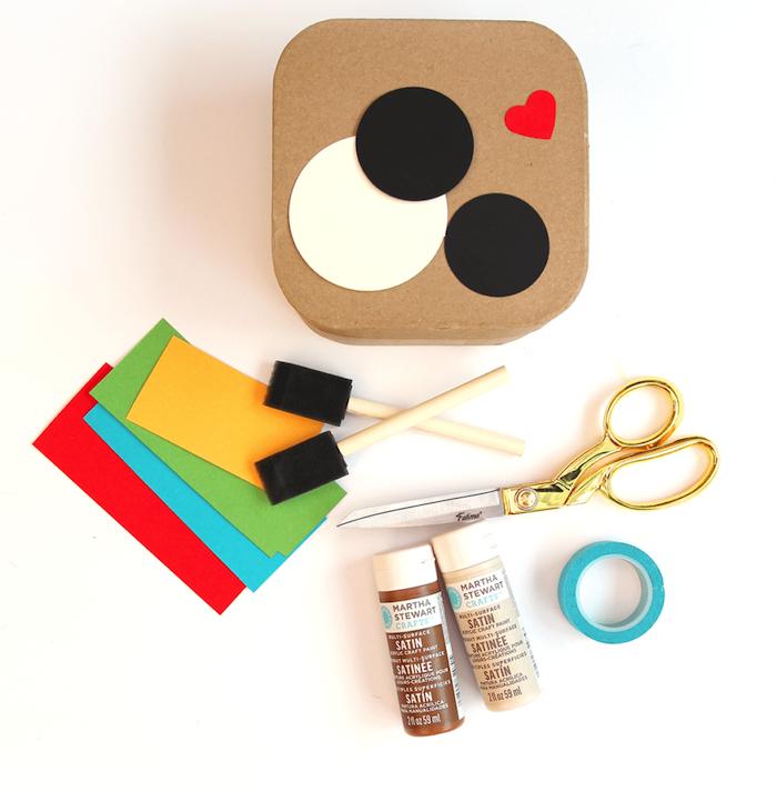 Materialien für DIY Glasuntersetzer in Form von Fotoapparat, Schwammpinsel und Schere, Acrylfarben und buntes Tonpapier