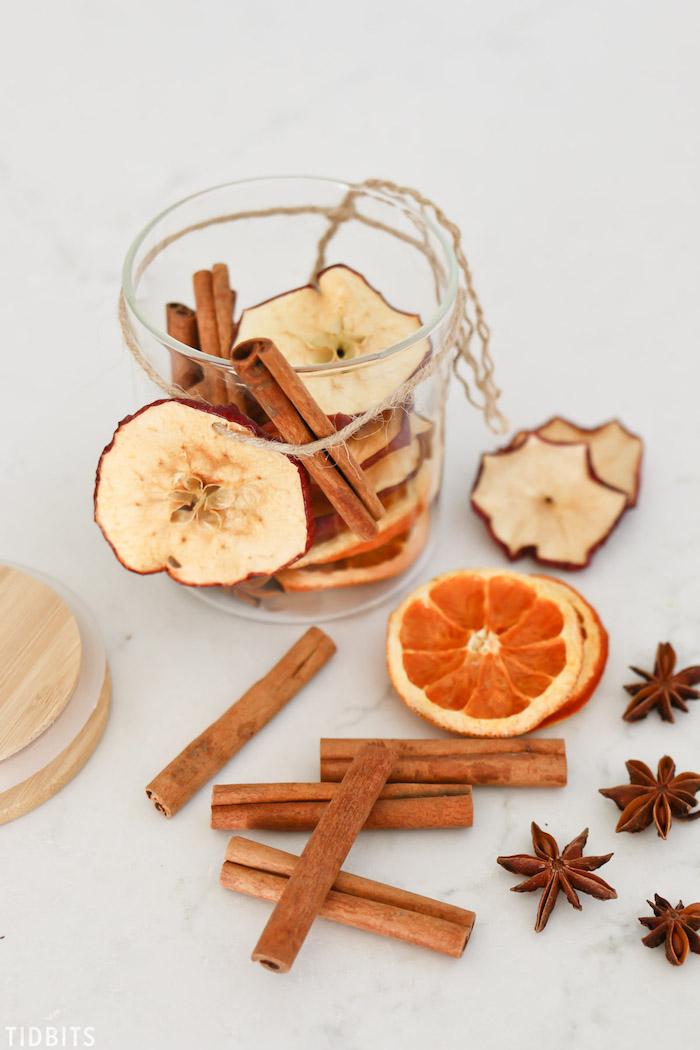 Getrocknete Orangenscheiben und Apfelscheiben, Zimtstangen und Sternanis in Einmachglas aufbewahren