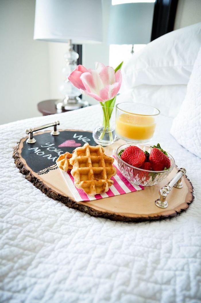 Frühstück im Bett, belgische Waffeln, Erdbeeren und Orangensaft auf Tablett, Tulpen in kleiner Glasvase