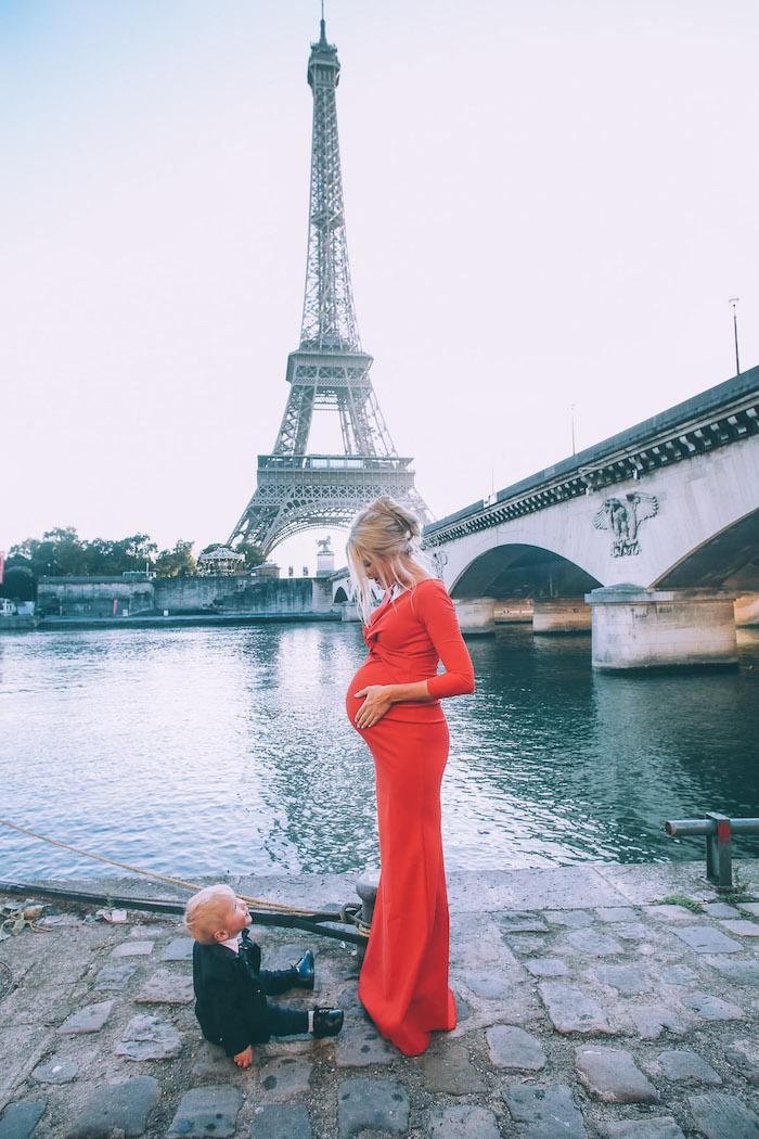 Langes rotes Umstandskleid für besondere Anlässe, lässige Hochsteckfrisur, süßer Junge auf dem Boden, der Eiffelturm im Hintergrund
