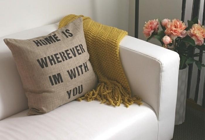 diy geschenke, ein kissen mit spruch und nette botschaft schenken, das zuhause ist da wo ich mit dir bin, weißes sofa mit deko kissen und decke, blumen daneben