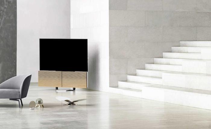 wohnzimmer mit weißen wänden und treppen und einem großen fernseher mit schwarzem bildschirm und zwei gelben flügel-lautsprechern
