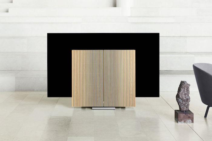 ein fernseher mt großem schwarzen display und zwei gelben großen lautsprechern aus aluminium, ein wohnzimmer mit weißen treppen