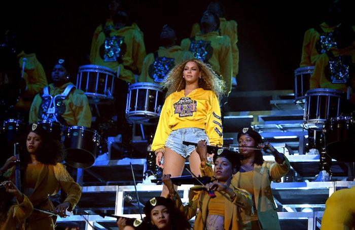 eine junge frau mit langem haar, die bühne von dem coachella festival. die sängerin beyonce mit gelbem pullover und kurzen blauen hosen