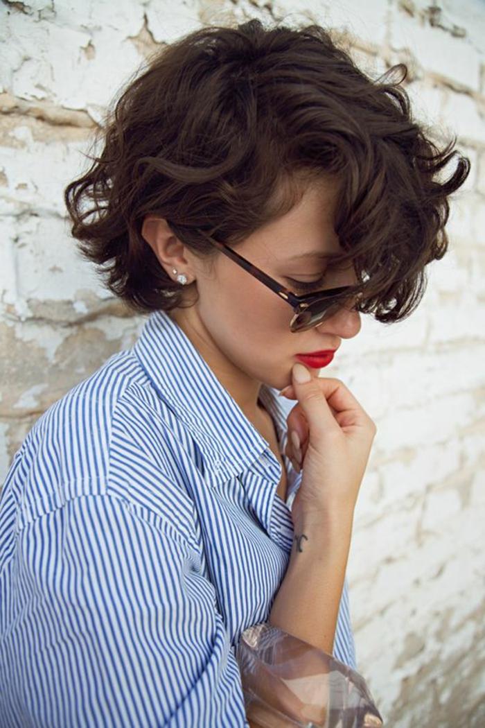 kreative bob frisuren, locken für kurzes haar, schwarze haare, moderne frisur, frau mit sonnenbrillen, blaues hemd und dezente ohrringe