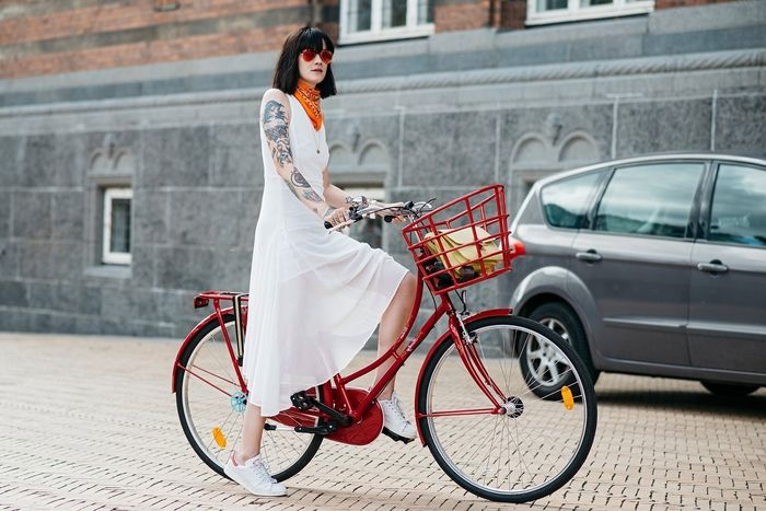 bob frisuren kurz, eine frau auf der straße mit ihren fahrrad, rotes rad, weißes kleid, schwarzes haar