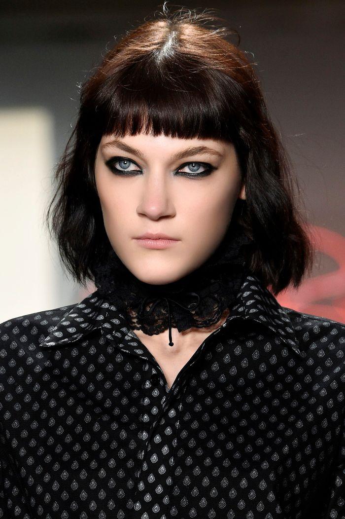 bob frisuren kurz, dunkle haare auf dem modepodium, hemd schwarz mit punkten, choker