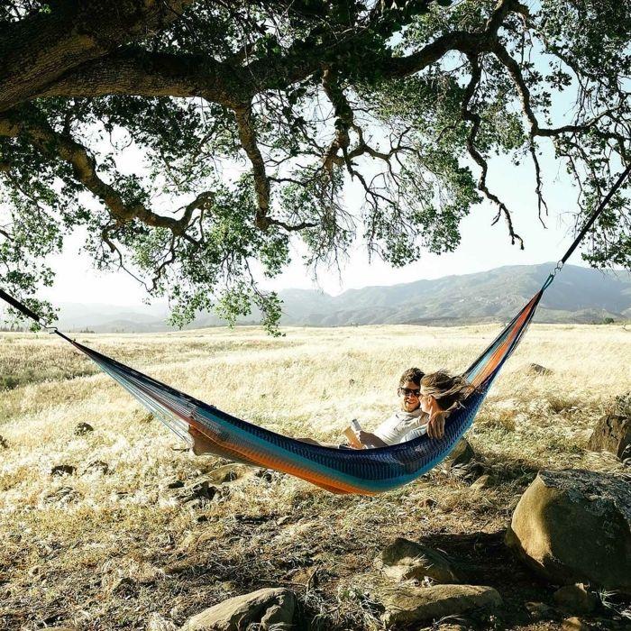geburtstagsgeschenk für freund, erlebnisgeschenk, mann und frau sitzen in einem hammock, baum