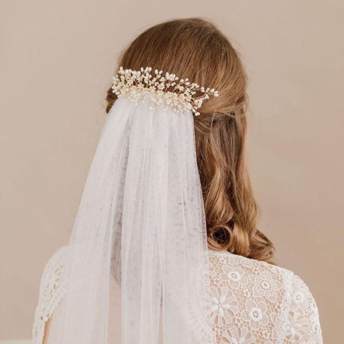 frisuren für hochzeit mit haarschmuck und schleier daran angehängt, weißer schleier, blonde haare mit locken