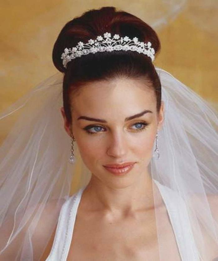 hochzeitsfrisuren lange haare gebunden gestalten, bob, hochsteckfrisur mit tiara und schleier, blauaugige braut mit dunklen haaren