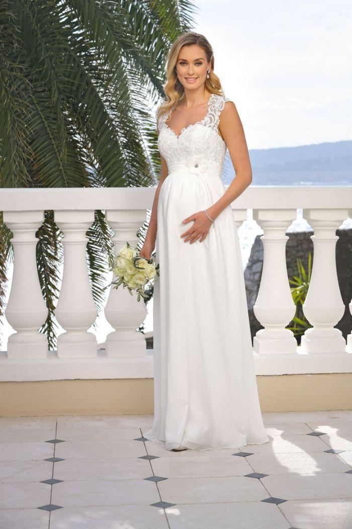 brautkleid schwanger standesamt, elegantes kleid, langes brautkleid, spitze und perlen als deko auf dem oberteil, blumen, foto auf einer terrasse