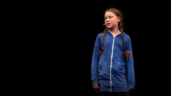 ein kleines mädchen mit langen zöpfen und einem braunen haar und blauen pullover, die schwedische klima-aktivistin greta thunberg