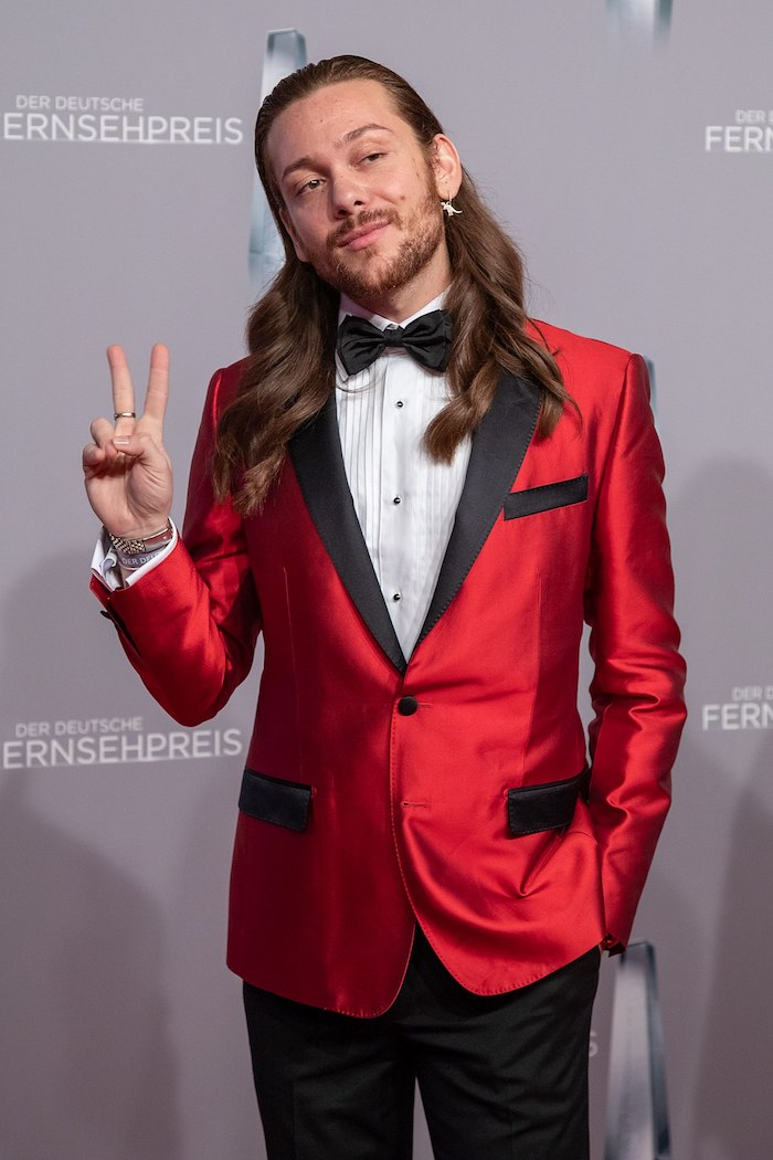 der deutsche blogger und model riccardo simonetti, ein junger mann mit rotem sakko und weißem hemt, schwarzer fliege
