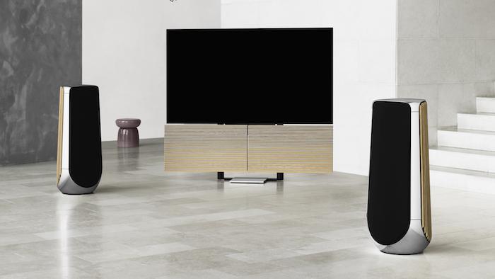 beovision harmony, zwei große schwarze lautsprecher, ein schwarzer fernseher mit zwei gelben klappbaren lautsprecher, ein wohnzimmer mit weißen und graueß wänden und weißen treppen